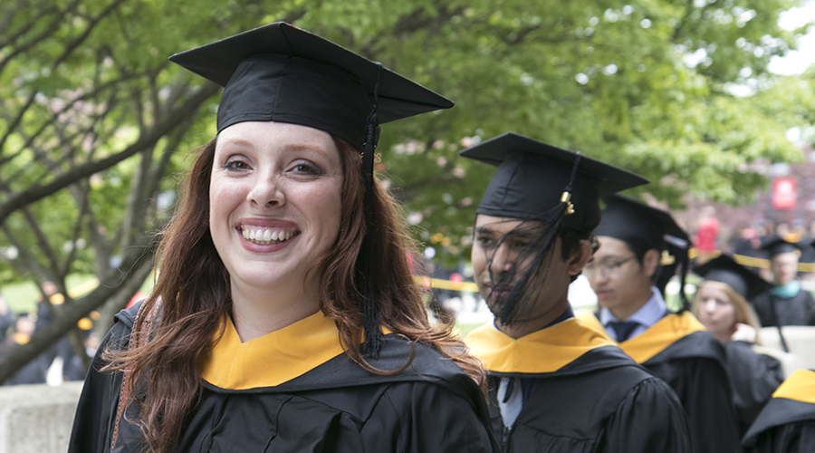 students walking with graduation gowns