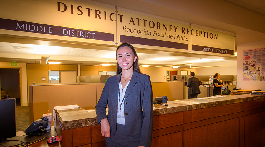 Female student sitting in front of District Attorney sign