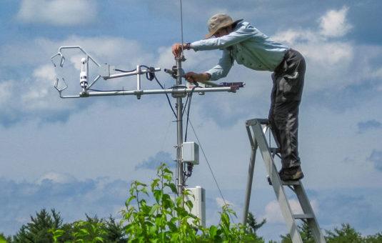 female standing on ladder adjusting equipment