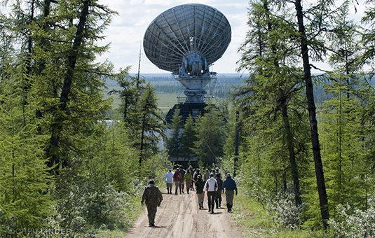 students walking to large satelite