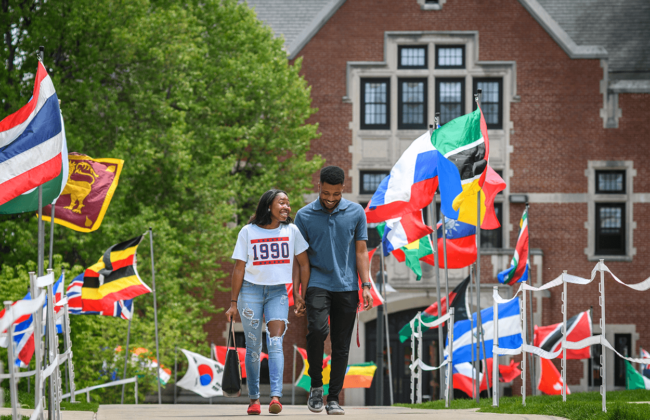 Students of color holding hands and smiling while surrounded by international flags.