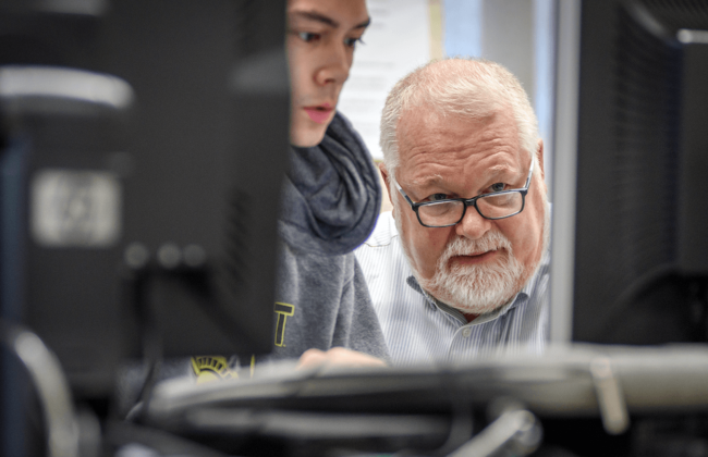 Image of student and faculty member looking at a monitor, working in a computer lab.