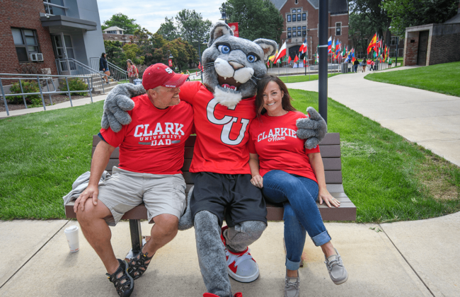 Image of two happy parents sitting on a bench with the Clark Cougar mascot.