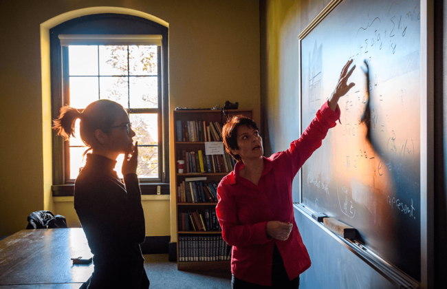 Two women working at a blackboard discussing physics equations.