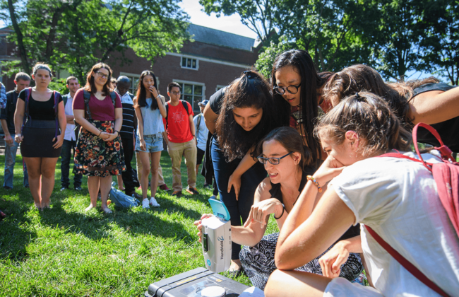Image of students outdoors, crowded around female professor as she shows them a piece of remote sensing equipment.