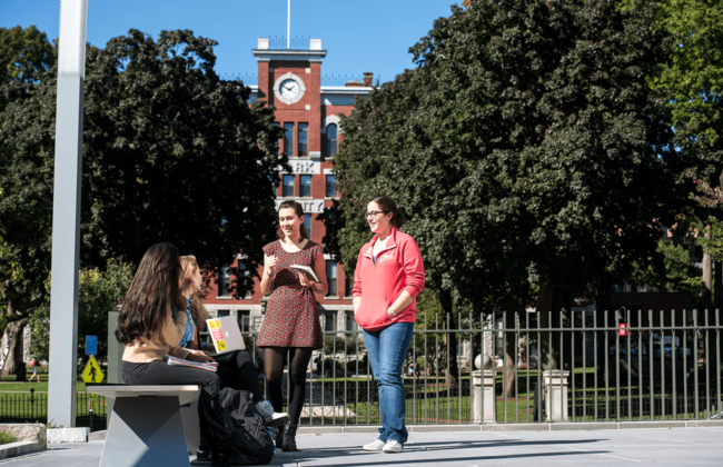 Image of students and standing having a conversation in front of Jonas Clark Hall.