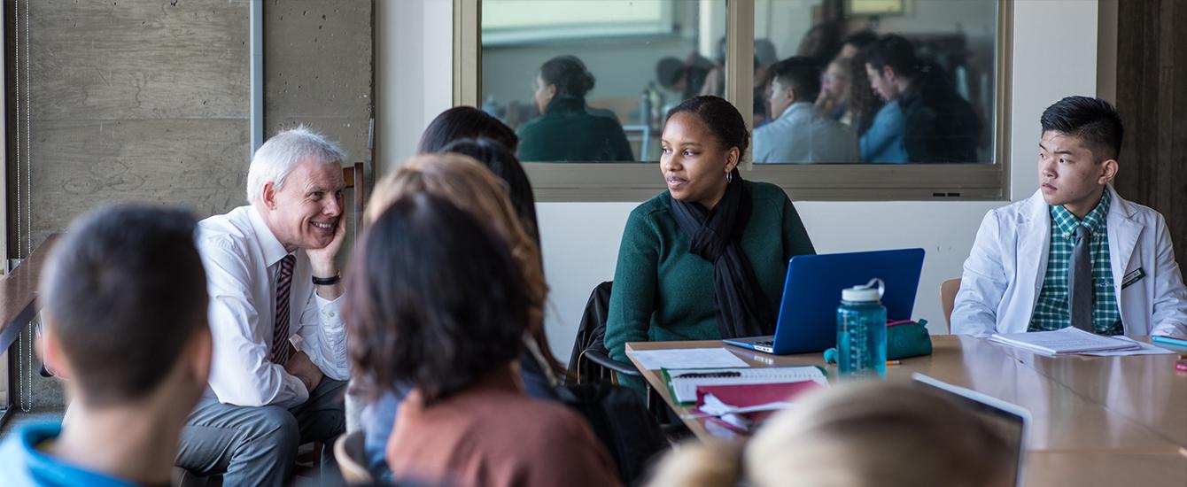 Clark University's President David Angel sitting in classroom