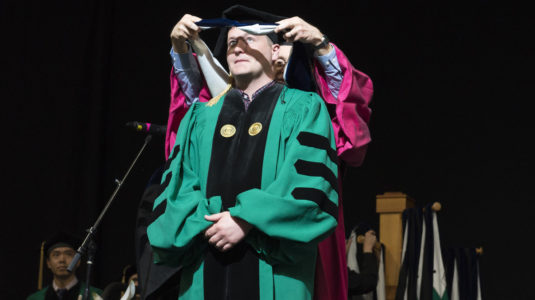 commencement ceremonyu with honorary degree recipient receiving award