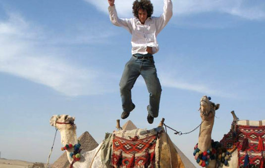 person jumping on a camel