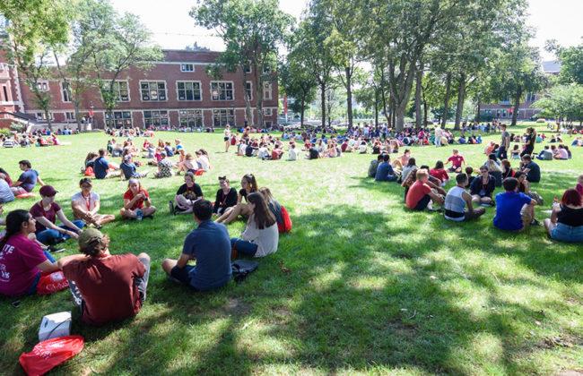 freshman student sitting on Clark's campus green