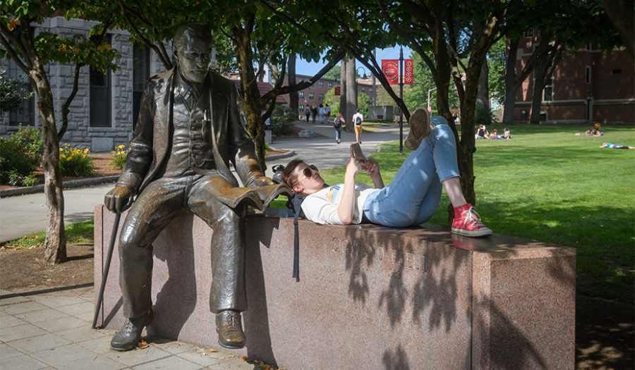 student leaning on statue