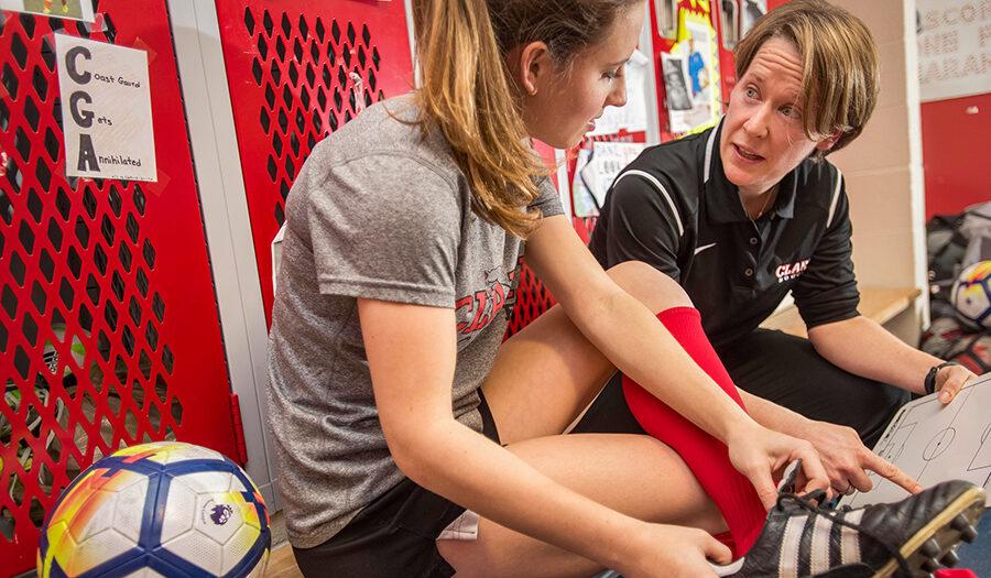 girls athletics coach talking to athlete