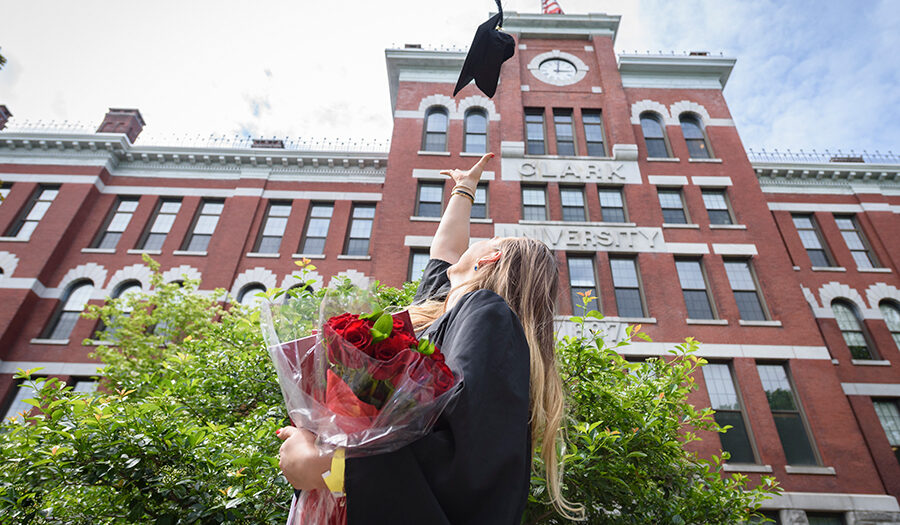 girl in graduation gown throwing up hat