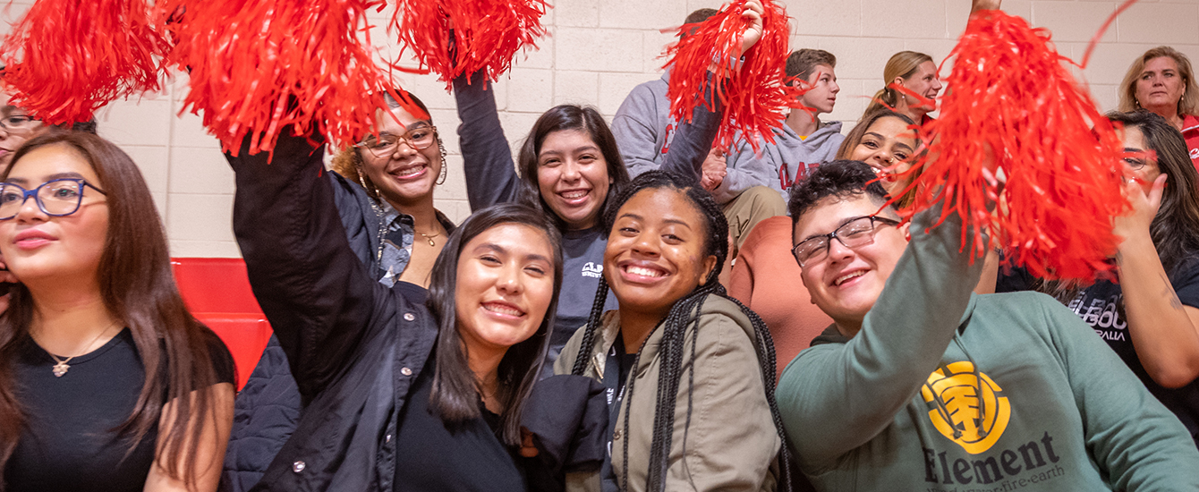 students in bleacher with pom poms