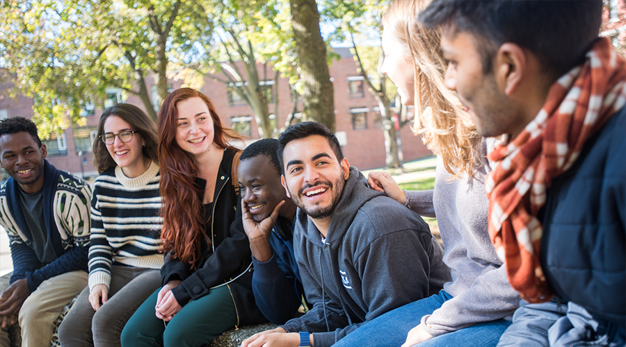 multicultural students sitting on bench
