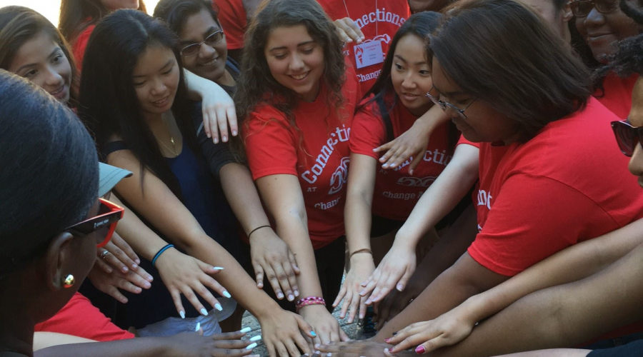diversed students putting in hands in a group