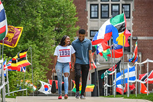 students walking down path with flags