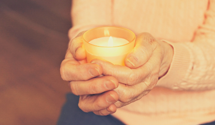 Elderly woman holding a candle