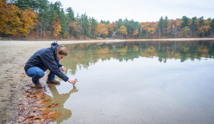 Student collecting water sample at Walden Pond