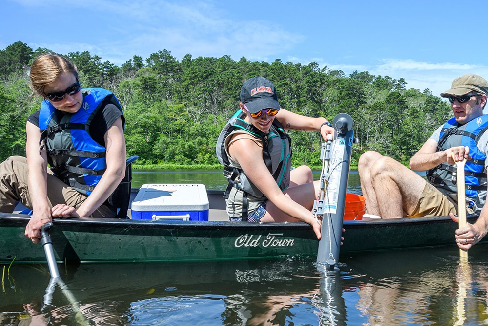 students in canoe collecting samples