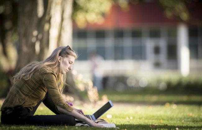 female student sitting on grass with lapto