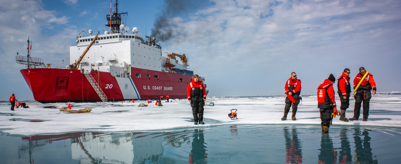 Coast Guard cutter sitting on iceberg with two students looking at sea.