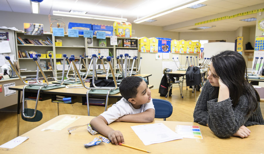 young k-6 student doing homework with Clark student