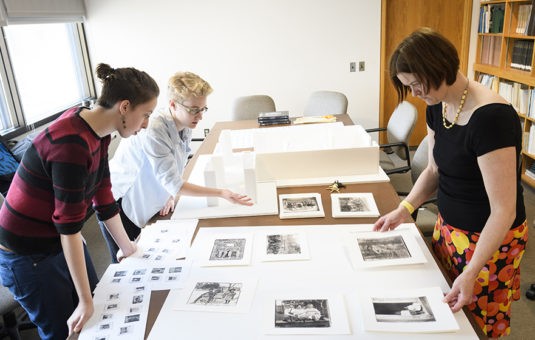 Students looking over drawings on table
