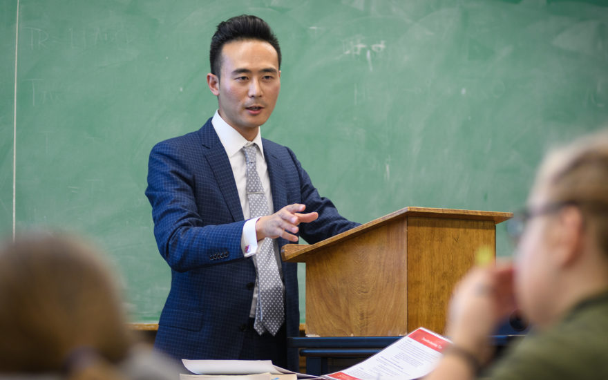 asian male standing in front of class at podium