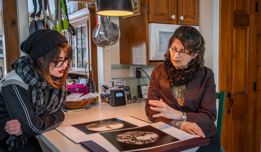 professor looking over art with student in kitchen