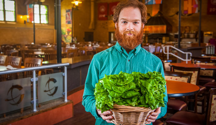 male holding basket of leafy greens