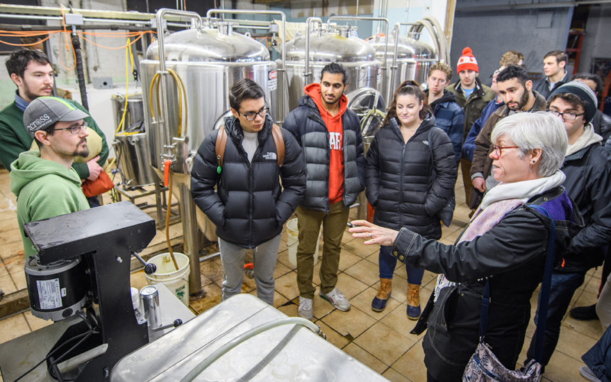 professor for economics major talking to students in beer factory