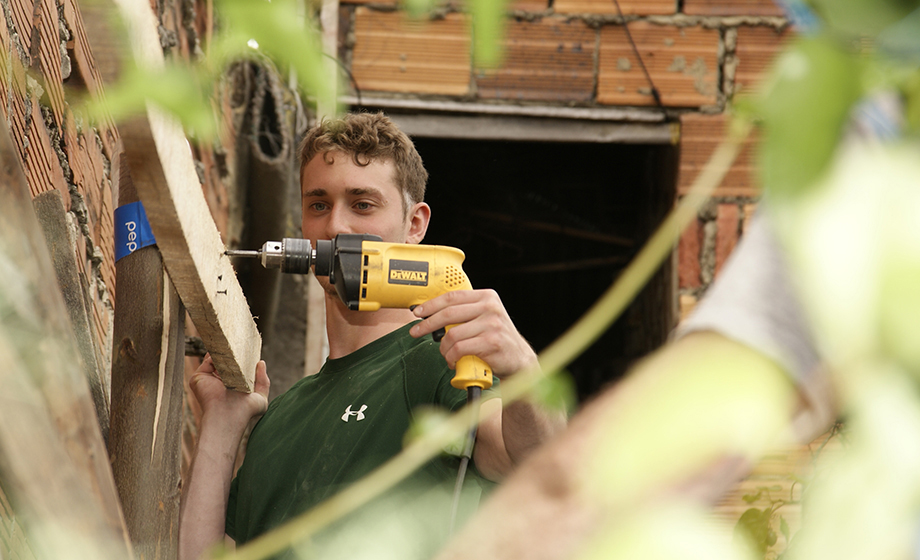 student drilling into wood