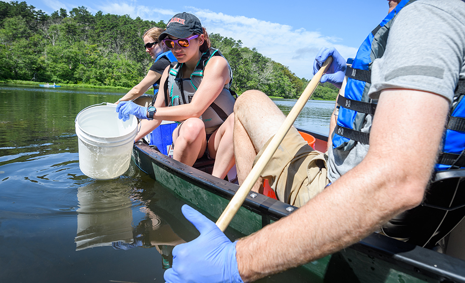 Students in canoe gathering up water samples