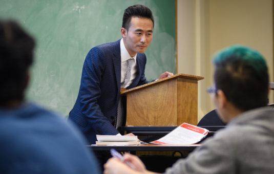 Professor leaning on podium