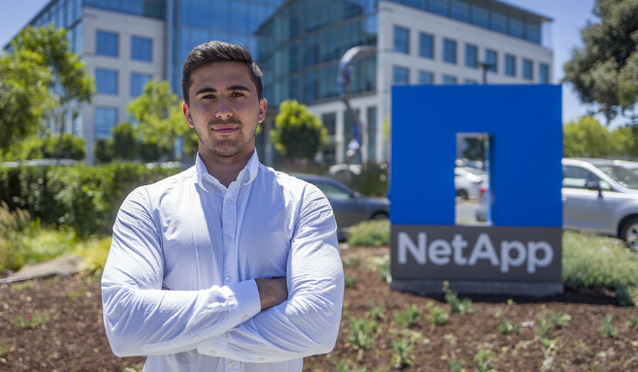 male student sitting in front of netapp sign