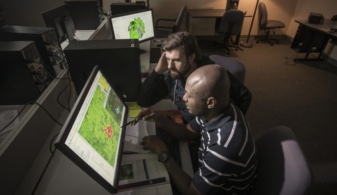 two males looking at heat maps