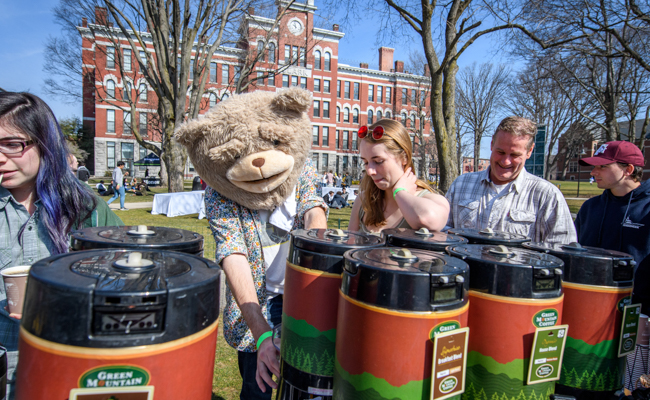 bear mascott raking with garbage bins