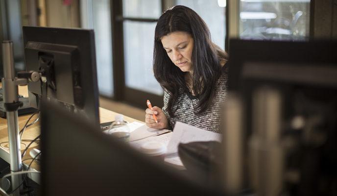 female student doing homework in library