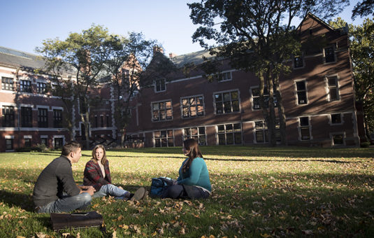 two students sitting on grass with fall leaves surrounding them