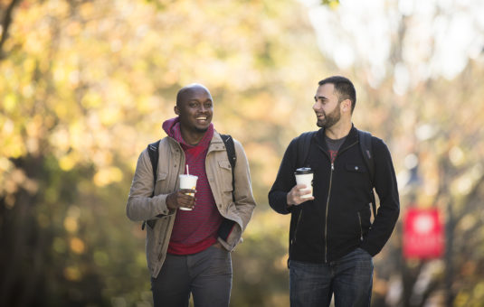 two male students walking with fall leaves behind the