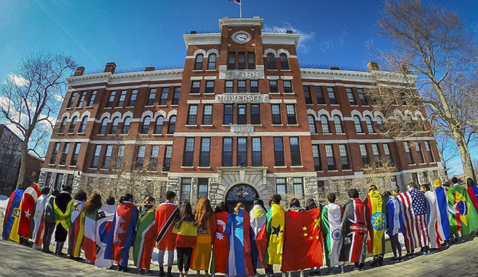 international students with colors standing in front of building