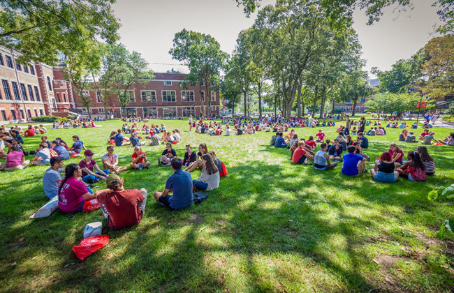 Students sitting on lawn in large group
