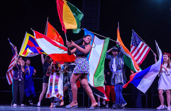performers on stage with flags