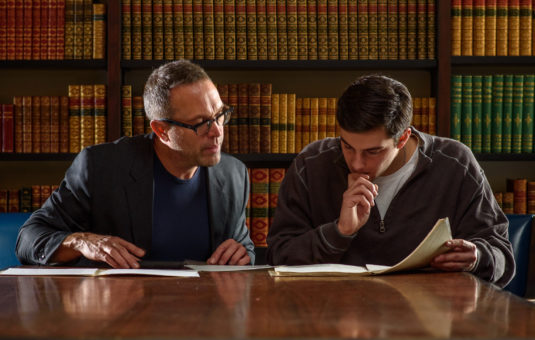 Professor and student sitting at table in library reviewing homework