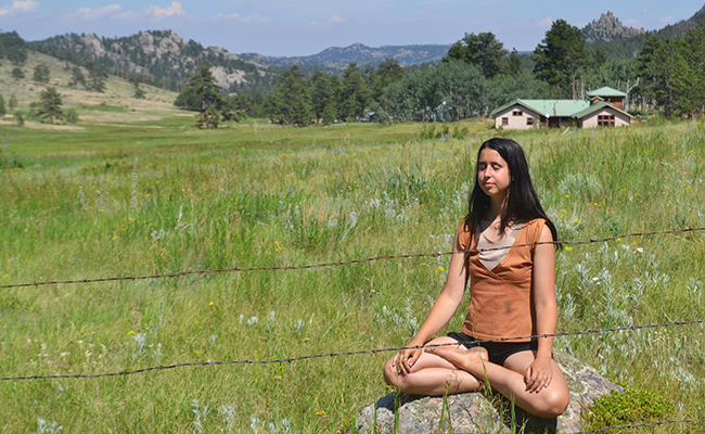 student sitting on rock in field mediating