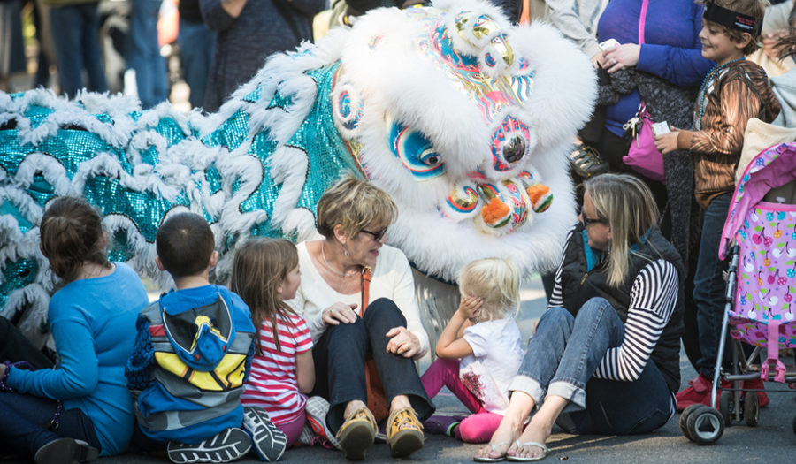 woman on the ground with children and chinese dragon