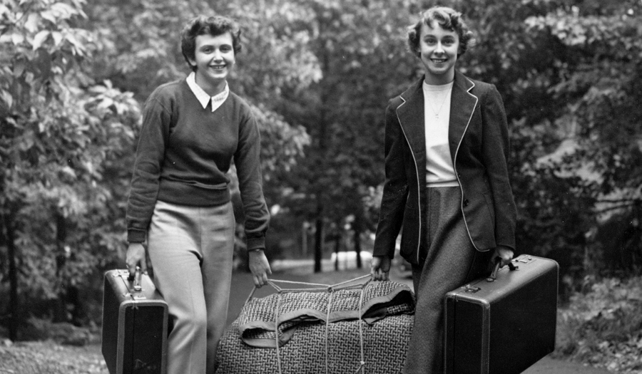 Two women carrying suitcases on campus
