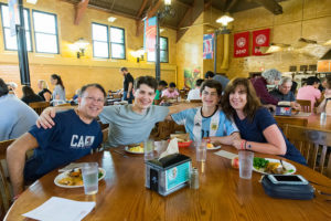 family smiling with arms around each other at dinning table