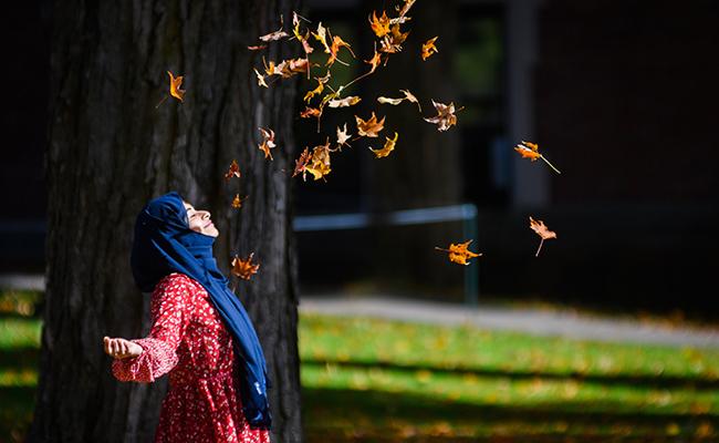 Female embracing falling leaves